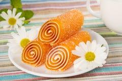 Orange färgrika godisar göra gelé av med blomman, bakgrund Royaltyfri Fotografi