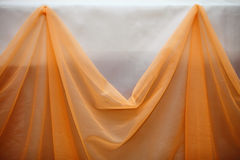 Orange fabric cloth and white wall decor detail Stock Photography