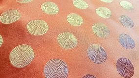 Orange fabric with golden color circular weaved patterns. Simplistic yet pleasing in design. Suitable for use in modern décor stock photo