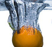 Orange falling in water. Orange falling into the water over white Royalty Free Stock Images