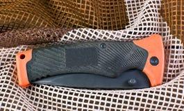 Orange faltendes Messer mit einem Eisengriff gut auf Militär-Camoufla Lizenzfreie Stockbilder