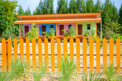 The orange fence. The colorful orange fence in front of colorful houses stock image
