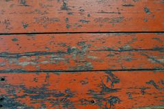 Orange fence of wooden planks. Old orange fence made of many wooden planks with peeled off paint, scratches and holes as a background stock photos