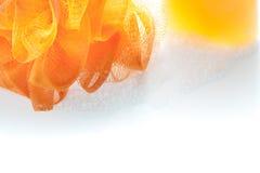 Orange fiber skurar, och duschen stelnar flaskan med bubblan på vita lodisar Royaltyfri Fotografi