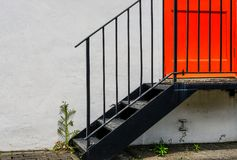 Orange fire door seen at the side of offices in central London. The lower half of the orange door is visible and weeds growing at the base of the stairwell Royalty Free Stock Photo