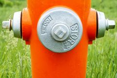 Orange Fire Hydrant. Detailed on a blue cloudy day with gray caps royalty free stock photos