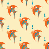 Orange fish with blue ornament on a beige background Royalty Free Stock Photos