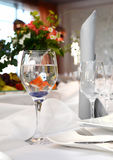 Orange fish swims in a glass. Little orange goldfish swimming in the glass, which stands on the festive table Royalty Free Stock Photography
