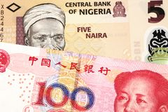 A Nigerian naira bill with with a Chinese yuan bank note close up. An orange five naira note from Nigeria with a red, one hundred yuan renminbi note from China royalty free stock photos