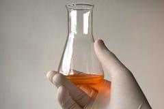 Orange Flüssigkeit in Erlenmeyer-Kolben Stockfotos