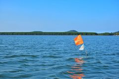 Orange flag embroidered in the sea. An orange flag embroidered in the sea to symbolize something for a fisherman`s boat stock photos