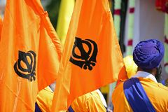 Orange Flags with sikhism symbol called Khanda. And a man with blue turban Stock Images