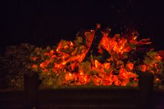 Orange flames in ash in fireplace Royalty Free Stock Images