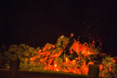 Orange flames in ash in fireplace Stock Image