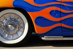 Orange flames on a blue roaster. Detail of highly customized car with orange flames on a blue roadster Royalty Free Stock Images
