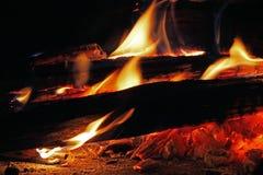 ORANGE FLAMMOR SOM HOPPAR UPP FRÅN, LOGGAR IN EN WOODFIRE arkivfoto