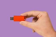 Orange Flash-Speicher an Hand mit violettem Hintergrund Lizenzfreie Stockbilder