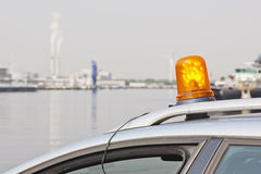 Orange flashing light. On top of a support and services vehicle in an industrial harbour Royalty Free Stock Photo