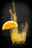 Orange flavoured soft drink splashing over the glass. Stock Images