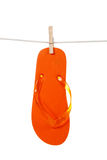 Orange flip - flop on clothesline Stock Photo