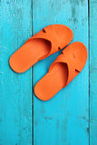 Orange flip flop sandals on blue wooden background Royalty Free Stock Images