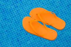 Orange flip flops floating in blue pool water Stock Photo