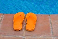 Orange flip flops on pool edge Royalty Free Stock Photography