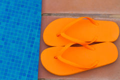 Orange flip flops on pool edge Royalty Free Stock Photos