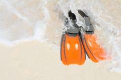 Orange Flipper auf dem weißen Sand und den Meereswogen Stockfotografie