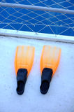 Orange flippers on boat dock Stock Images