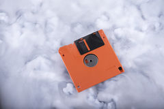 Orange floppy disk in the clouds Royalty Free Stock Photo