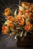 Orange Flower Bouquet. Artificial orange flower bouquet on dark brown wooden table Royalty Free Stock Images