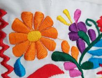 Orange flower embroidered on fabric. Background texture, fashion and style, backdrop for advertisements of clothes in spring, thread and cotton material Royalty Free Stock Photography