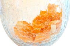 Orange flowers petals on cracked glass vase. Royalty Free Stock Photo