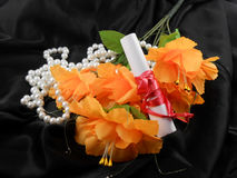 Orange flowers, white paper and diamonds on black background Stock Image