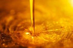 Orange flytande och viskös ström av motorisk olja för motorcykel som ett flöde av honungnärbilden royaltyfria bilder