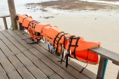 Orange flytvästar på trä, för badhavet Arkivfoton