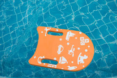 Orange foam board floating in swimming pool.  royalty free stock images