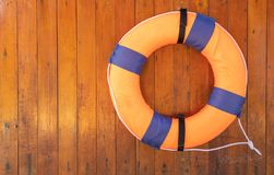 Orange foam life buoy on wood wall stock photos