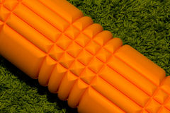 Orange foam roller on green background stock image
