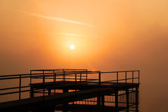 Orange fog. On a photo the fine morning dawn painted orange tone and powdered by an easy smoke of a morning fog is represented Royalty Free Stock Images