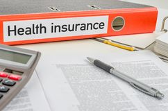 Health insurance. An orange folder with the label Health insurance Royalty Free Stock Photography