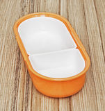 Orange folding plastic food box on the wooden background, kitche. Orange folding plastic box for food storage on the wooden background. Kitchen equipment Royalty Free Stock Images