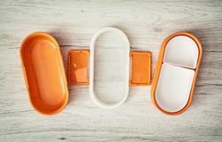 Orange folding plastic food box on the wooden background Royalty Free Stock Images