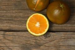 Orange-foncé d'isolement sur le fond en bois Oranges de Brown photo stock