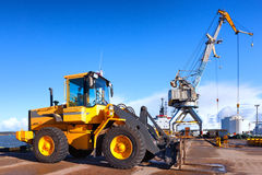 Orange forklift and crane at loading and unloading of cargo in t Royalty Free Stock Photos