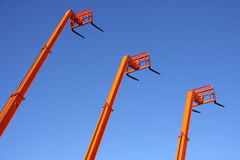 Orange Forklifts. Under a Vivid Blue Sky Stock Photos