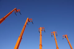Orange Forklifts. Under a Vivid Blue Sky Stock Photo