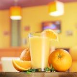 Orange Früchte und Glas Orangensaft Stockbilder