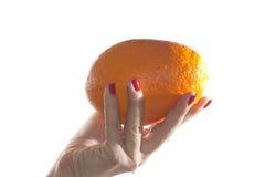 Orange fraîche chez la main du ` s de la femme Photographie stock libre de droits